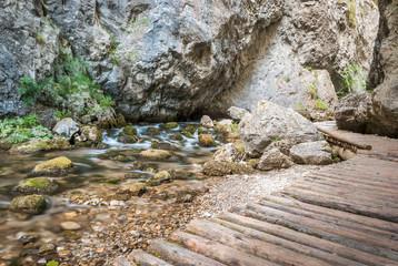 creek under rocks with wooden footpath