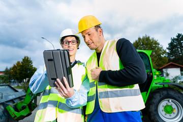 Bauarbeiter diskutiert Bauplan auf Baustelle