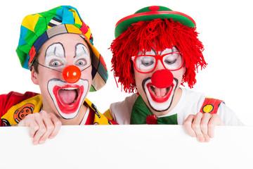 clowns schauen begeistert auf schild