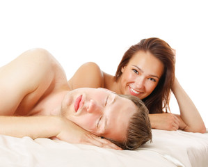 A couple is lying in bed on white background.