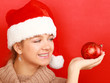 Young woman on santa hat holding Christmas ball