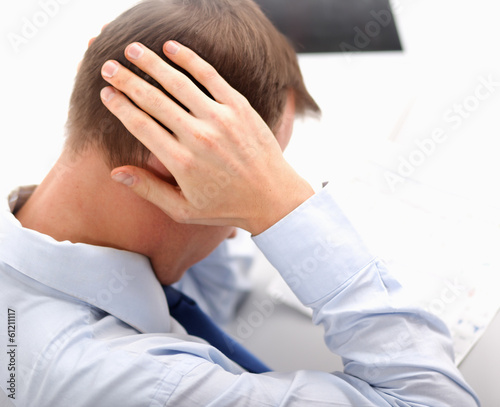 A businessman with a headache, sitting at the desk.