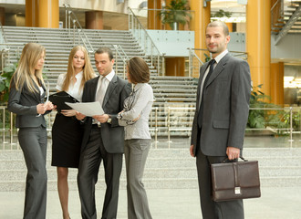 Portrait of business people standing in the office with folder