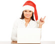 Young woman in santa hat sitting with laptop