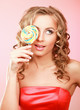 young happy woman with lollipop, isolated on pink background.
