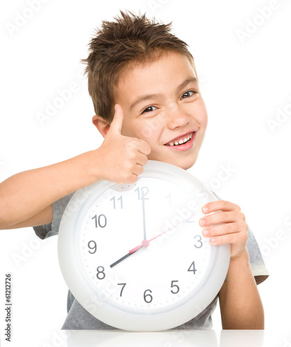 Boy is holding big clock