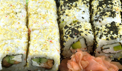 Portions of sushi rolls with salad and ingredients closeup
