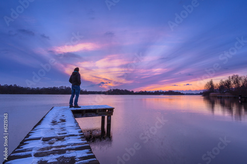 Man Watching the Sunset From a Pier