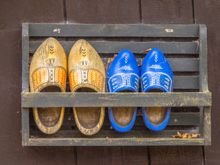 Two Pair of Dutch Wooden Shoes in a Rack on the Wall