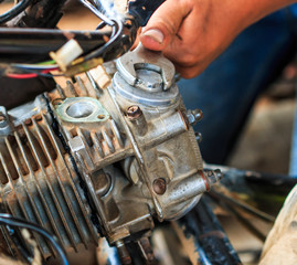 Technician is fixing a part of motorcycle