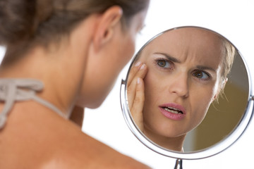 Concerned young woman looking in mirror