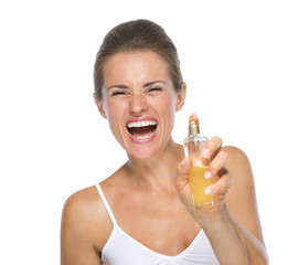 Happy young woman applying perfume in camera