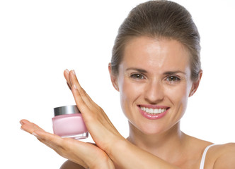 Happy young woman showing creme
