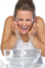 Happy young woman washing face in glass bowl with water