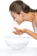 Profile portrait of woman washing face in glass bowl with water