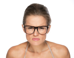 Young woman in eyeglasses looking attentively in camera