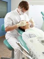 Young woman with dentist in a dental surgery.