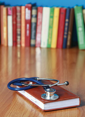 Stethoscope on book with leather cover.