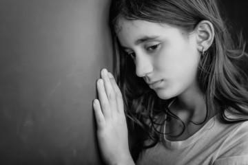 Grunge black and white portrait of a sad teenage girl