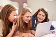 Three Teenage Girls Using Laptop In Bedroom