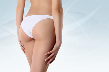 Bum and legs of slim woman over white background