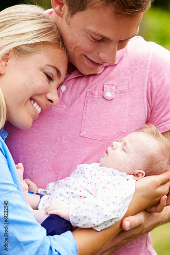 Proud Parents Holding Baby Daughter In Garden