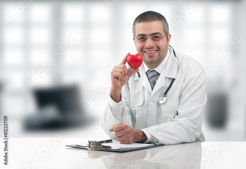 Doctor sitting at his desk with stethoscope holding heart