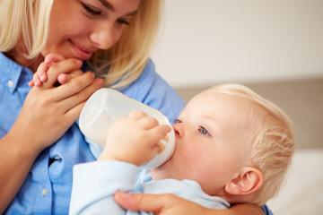 Mother Giving Baby Son Bottle Of Milk