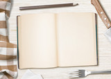 blank cooking recipe notes or book  with pencil on kitchen table