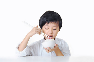 Asian boy eating white rice with chopsticks