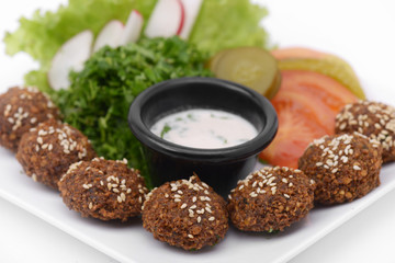 Falafel dish with veggies and tartar sauce