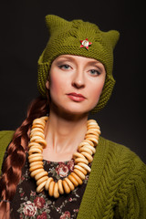 Girl in Russian style and red star posing in green  cap bagels o