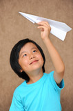 Cute Asian boy playing with paper plane