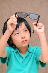 Asian boy looking at his glasses