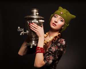 Girl in soviet retro style posing with samovar. Girl with a gree