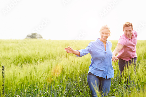Romantic Couple Running In Field Holding Hands