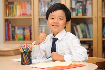 Smart Asian schoolboy sitting at a desk with thumbs up