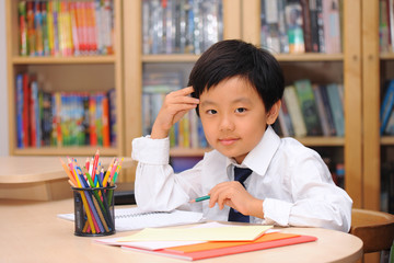 Schoolboy wearing white shirt and tie sitting at a desk