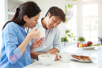 Asian Couple Reading Newspaper At Breakfast