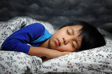 Cute boy having nightmare with dark clouds background