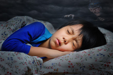 Boy having a scary dream (witch in dark clouds hanging above)