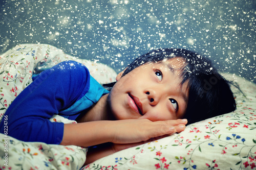 Cute young Asian boy dreaming of winter snow