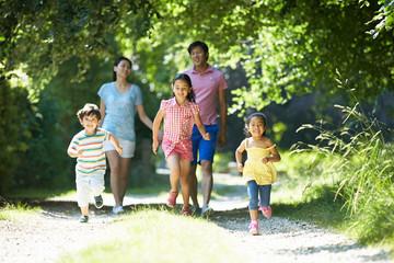 Asian Family Enjoying Walk In Countryside