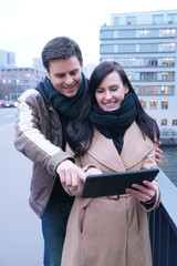 Young couple in the city looking at tablet computer