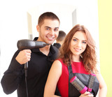 Young man and  woman hairdressers in beauty salon