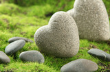 Grey stones in shape of heart, on grass background