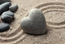 Szary zen kamień w kształcie serca, na tle piasku