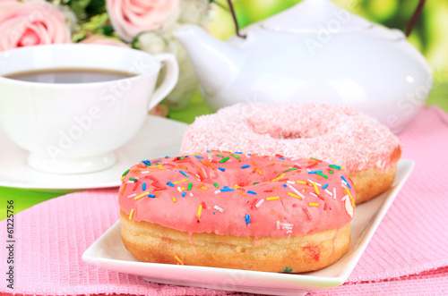 Sweet donuts with cup of tea on table close-up