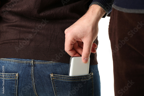 Pickpocket are stealing mobile phone from back pocket, close