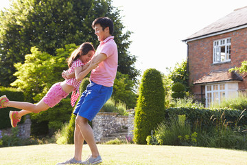 Asian Father And Daughter Playing In Summer Garden Together